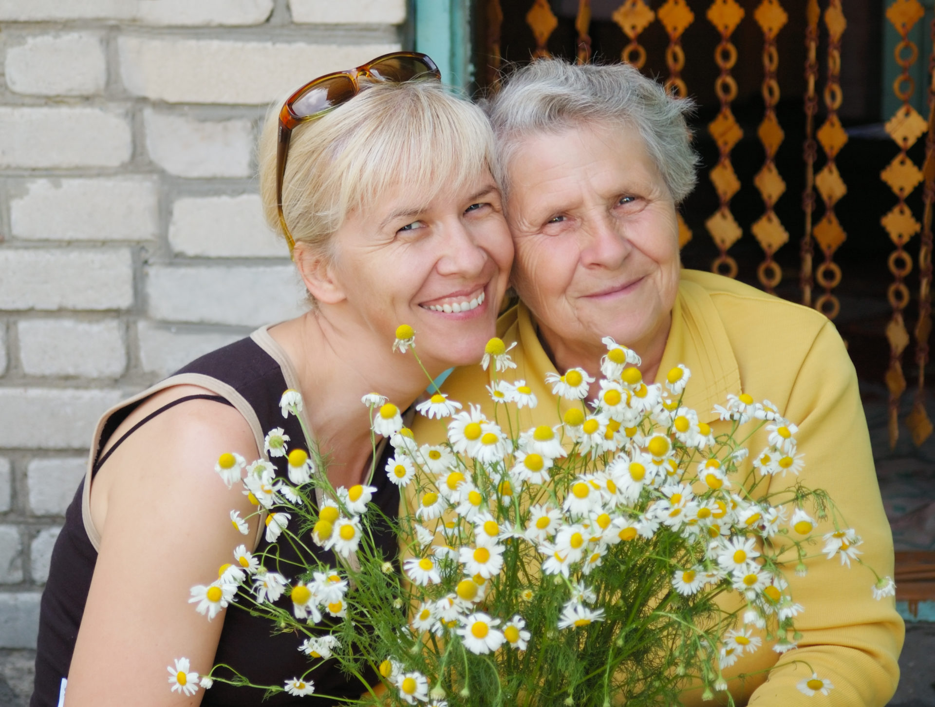mother with daughter take bouquet of camomile