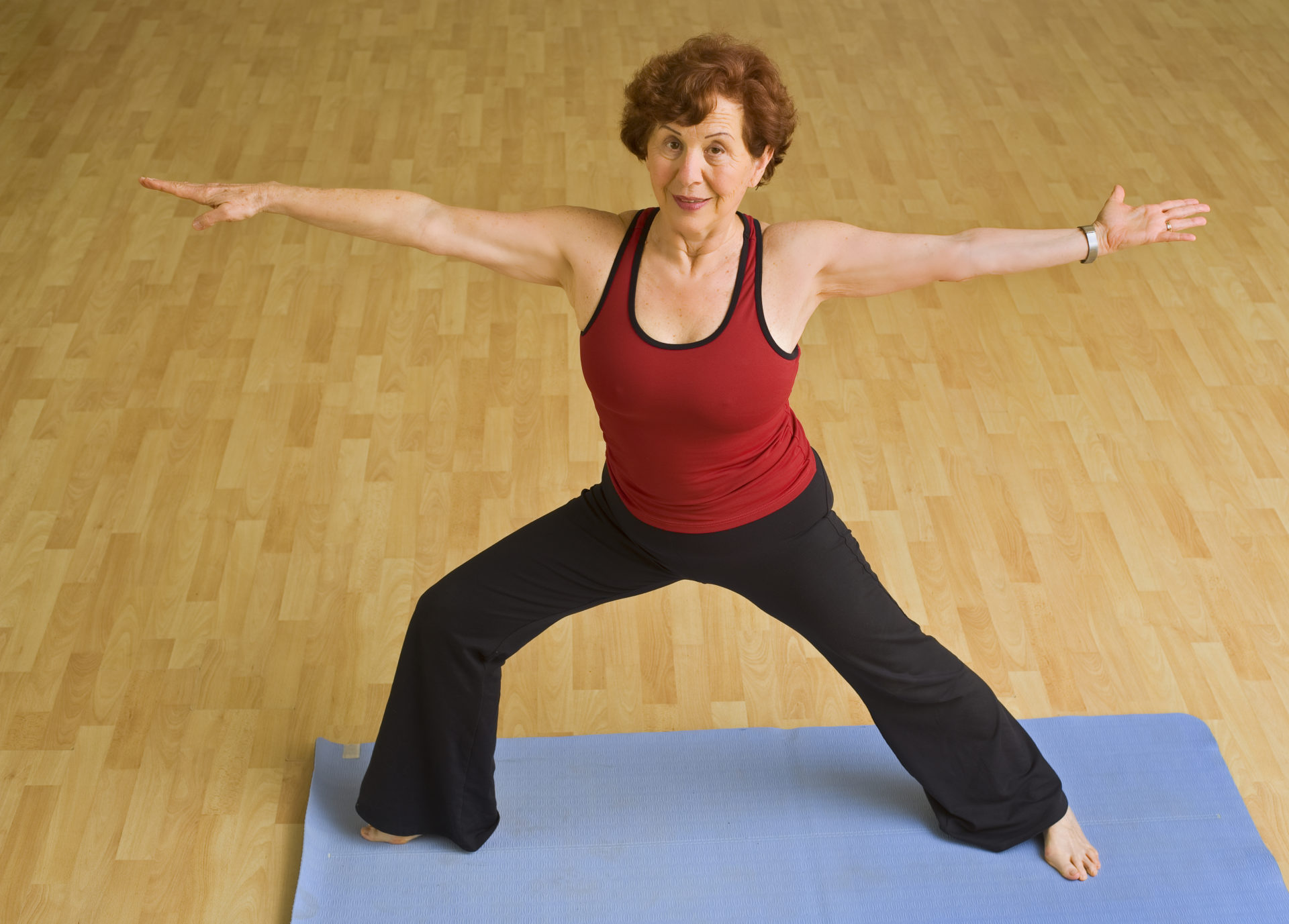 senior woman doing yoga in a gym